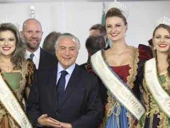 O presidente Michel Temer, entre a rainha e as princesas da Oktoberfest, durante cerimônia de sanção da lei que confere à cidade de Blumenau o título de capital nacional da cervejaAntonio Cruz/ Agência Brasil