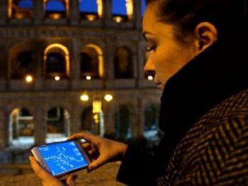 Mulher observa celular à noite Foto: BBCBrasil.com